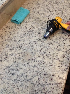 Using heat gun and acetone to bring out a stain in a granite countertop.